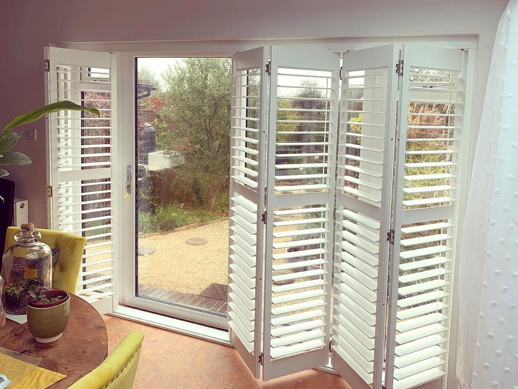 A shutter track system provides a great looking and practical solution for access to a patio garden.