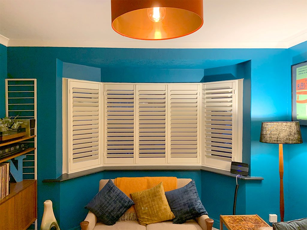 A stunning lounge interior design with white window shutters.